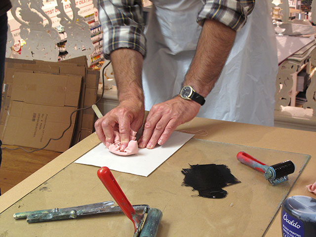 """3. Place a sheet of paper onto the ink covered lino and rub firmly. Lee has invented the """"wooden spoon wrapped in fabric"""" technique!"""